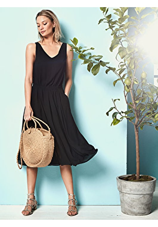 Model wears our stunning black dress combines our flowing midi skirt with a relaxed top with a semi sheer hem