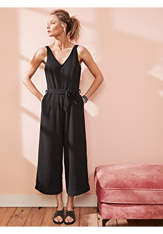 Model wears our jumpsuit with a detachable belt, wide leg trousers and a v neckline in black