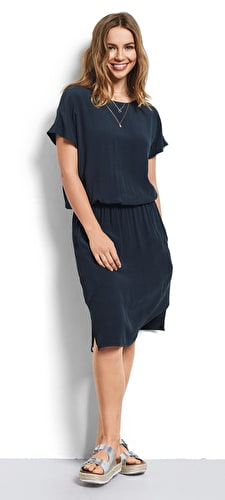 Model wears relaxed dress with an elegant v back and a scoop neckline and short sleeves in stunning blueberry colour