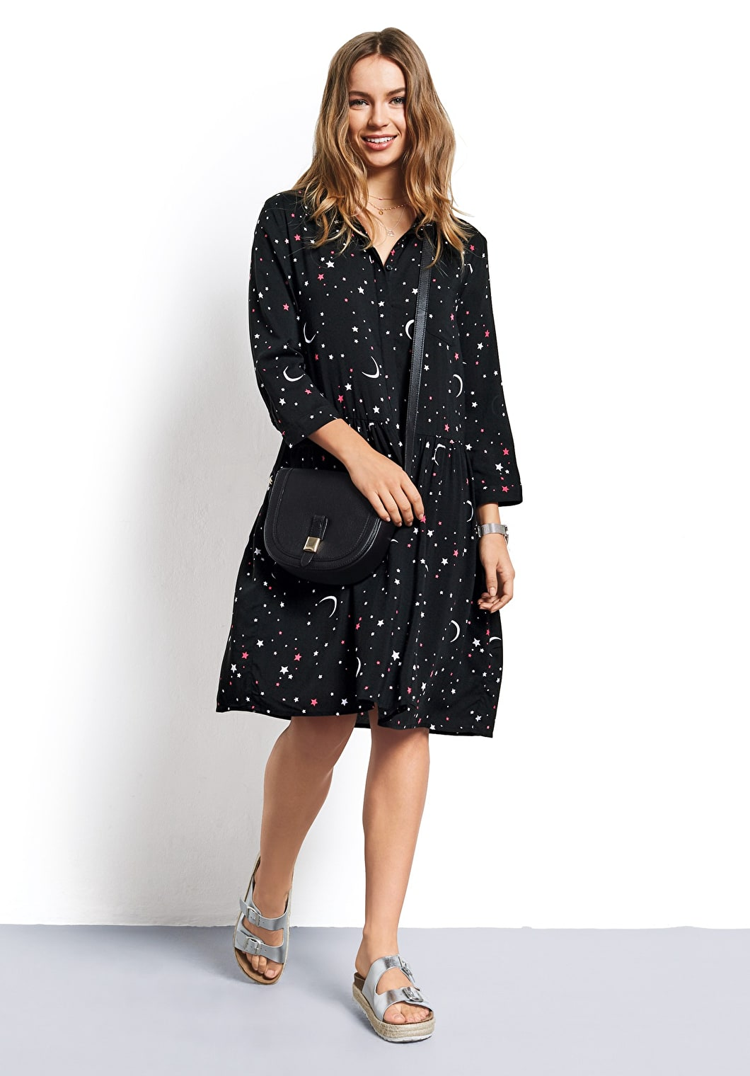 Women wears our cosmic inspired printed shirt dress with moons and stars with 3/4 length sleeves
