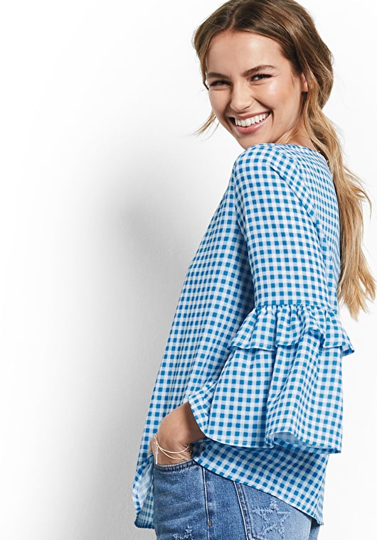 Model wears our Printed top with bell sleeves with a ruffle trim in gingham french blue and white