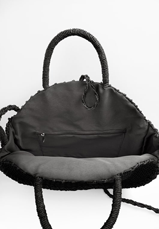 black round woven bag with a crossbody strap and handles with knot and loop fastening and a zip in the lining