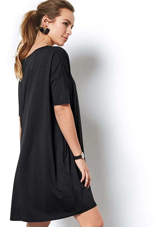 Model wears our modern take on an oversized t shirt dress in a classic black with a scoop neck and short sleeves