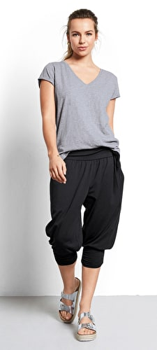 Model wears our harem trousers cropped just below the knee in black