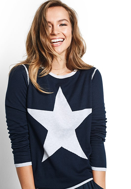 Model wears our standout reversable knitted star motif knitted jumper in grey marl and midnight