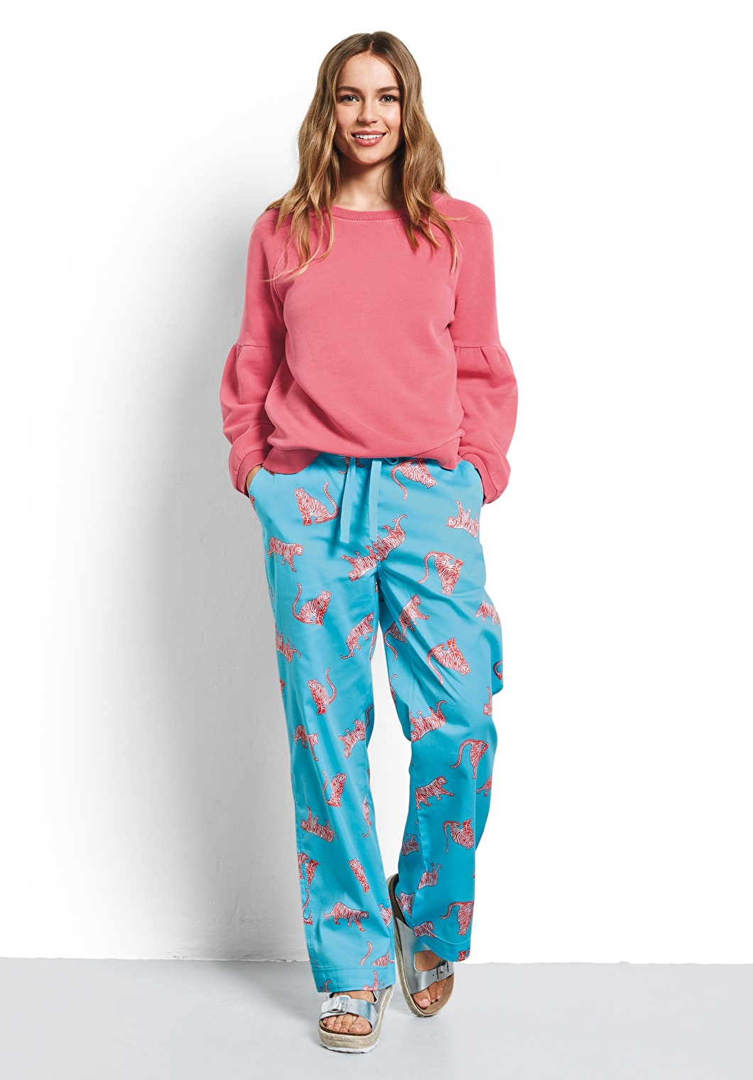 Model wears our Tiger print cotton pyjama trousers in radiance and coral