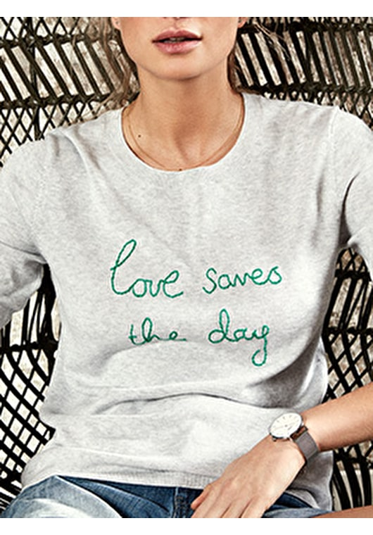 Model wears our embroidered 'Love saves the day' knitted jumper in grey marl and jolly green