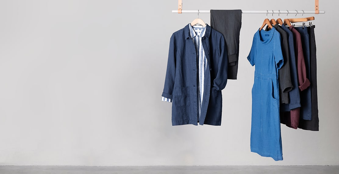 Different shades of blue linen shirts and dresses, Hanging from a clothes rail