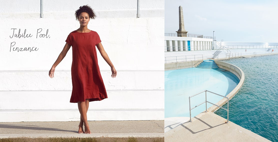 Girl wearing a long red linen dress at Jubilee Pool in Penzance.