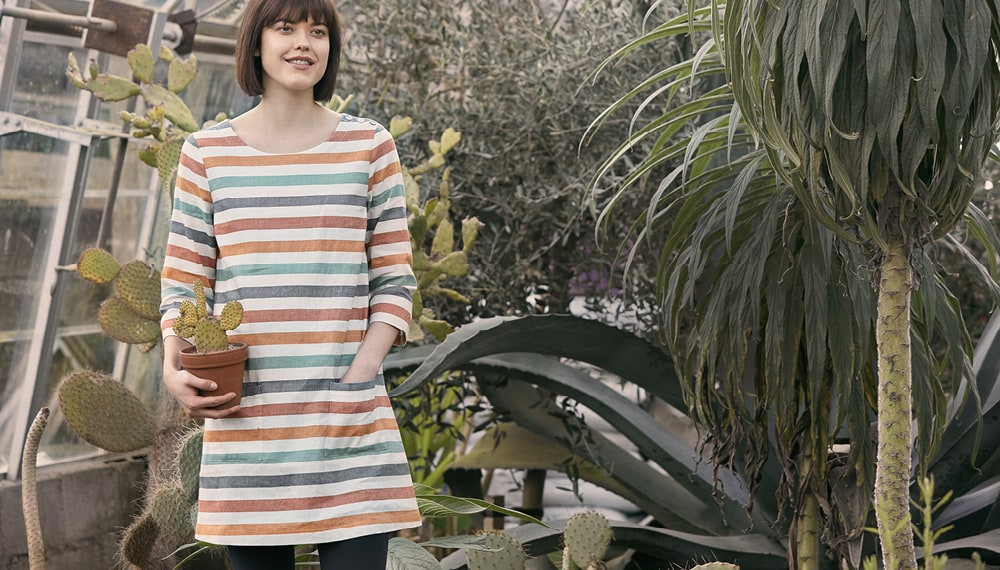 Dark haired lady wearing a stripey tunic holding a cactus at Potager Gardens