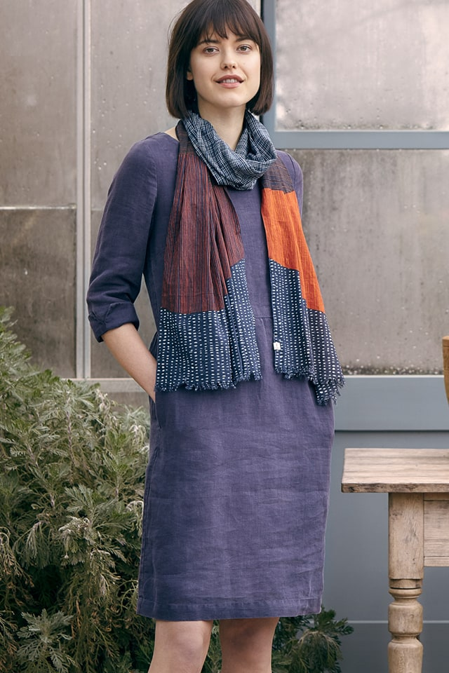 Dark haired lady wearing a navy tunic dress and a tasseled scarf