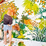 Lady painting flowerly scene on wall