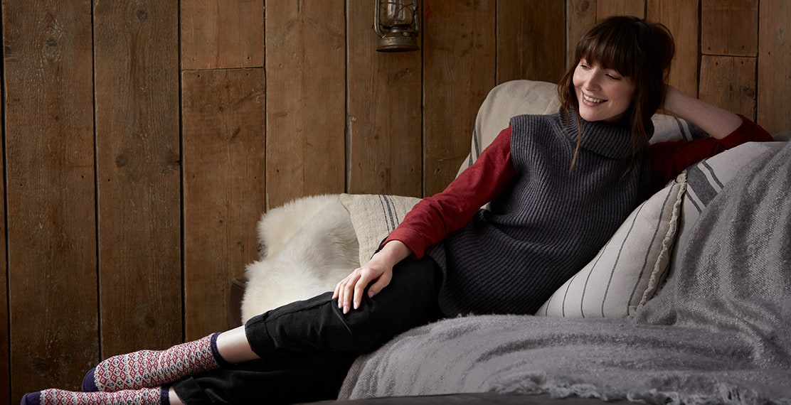 Woman laying on a comfy sofa wearing a woolen turtleneck