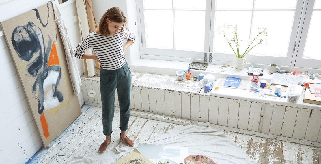 Women wearing a Stripey top & teal trousers admiring her artwork on the wooden floor of the studio.