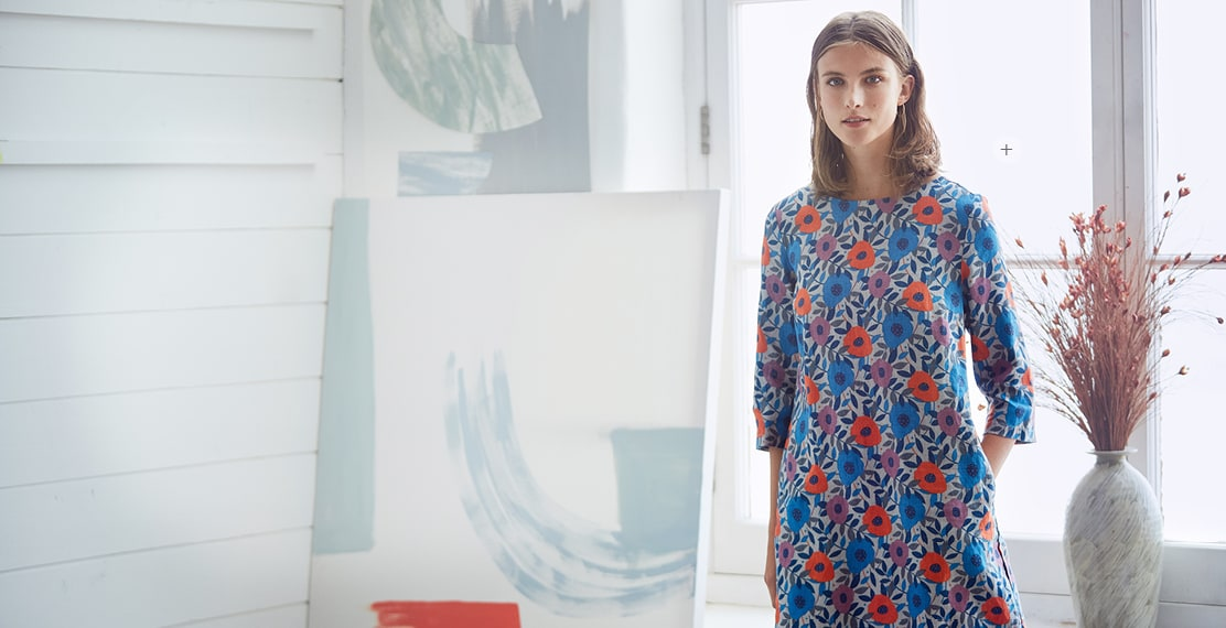 Women wearing A colourful Flower patterned dress next to a vase of flowers.