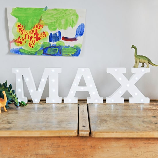 White light up letters on a shelf spelling 'Max' featuring toy dinosaurs