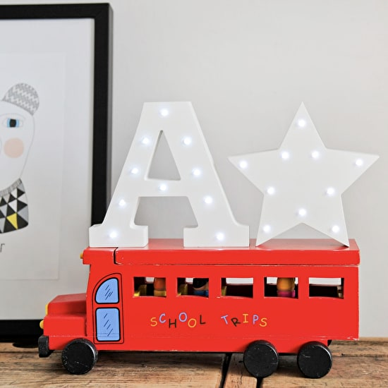 Lifestyle image of a white light up letter A and Star, on a toy school bus on a shelf
